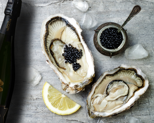 Opened oysters with black sturgeon caviar and lemon on ice on grey concrete background. Top view, flat lay, copy space